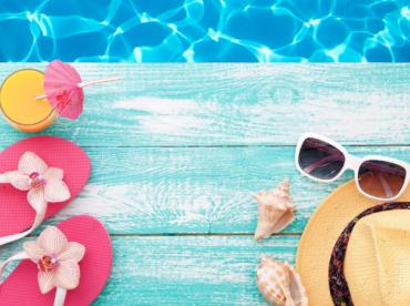 Imagem de piscina com apetrechos de verão próximos, como óculos escuros, chapéu e sandálias.