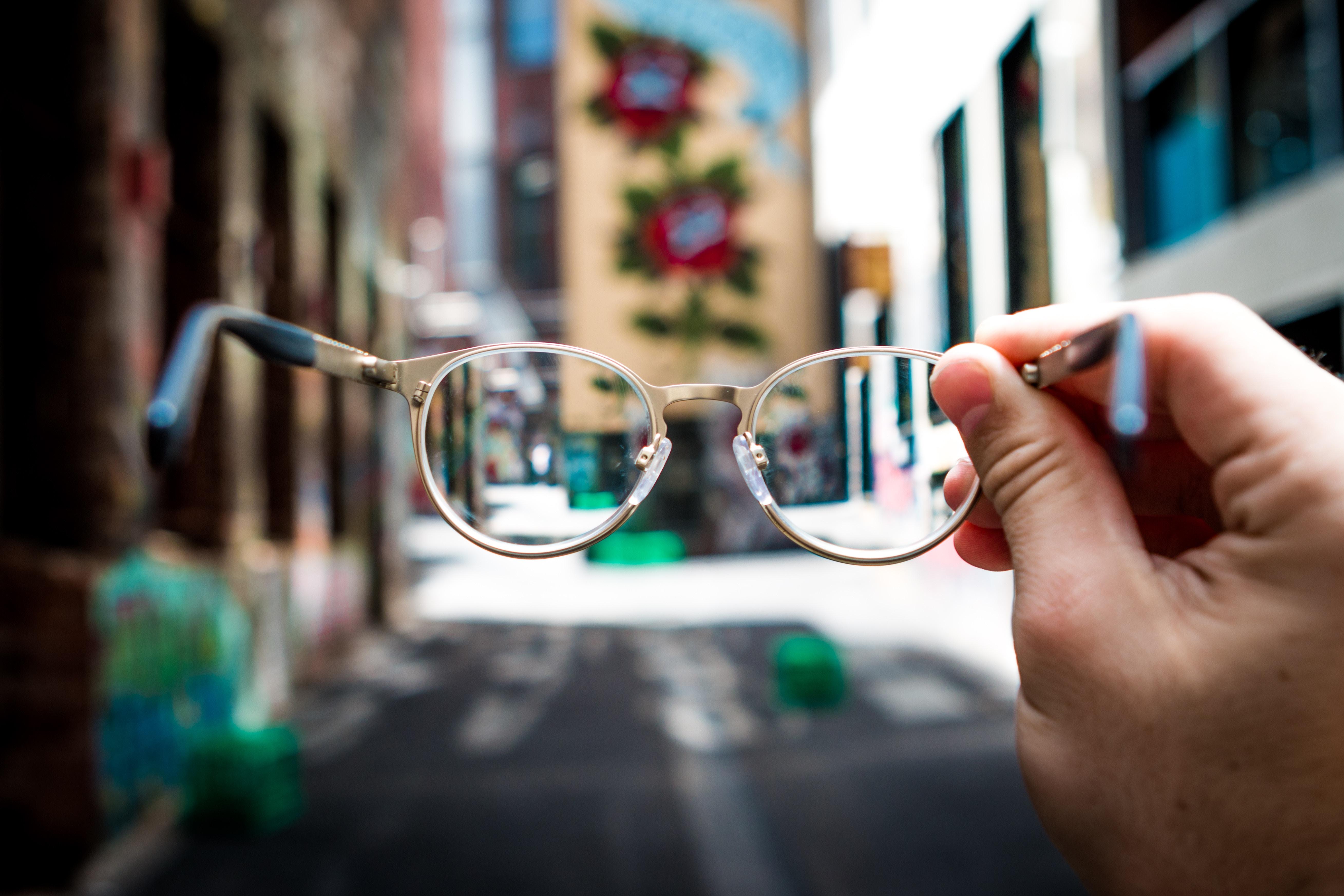 mão segurando óculos de grau na frente de um prédio grafitado. fora do óculos está tudo embaçado, pelas lentes a imagem está nítida.