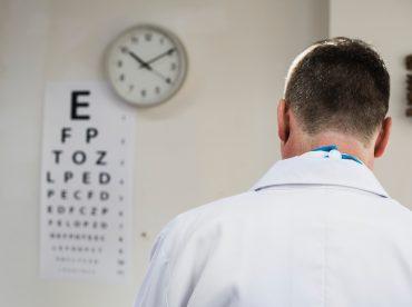 médico de vista olhando para a parede, onde tem um relógio e um cartaz com letras de diferentes tamanhos