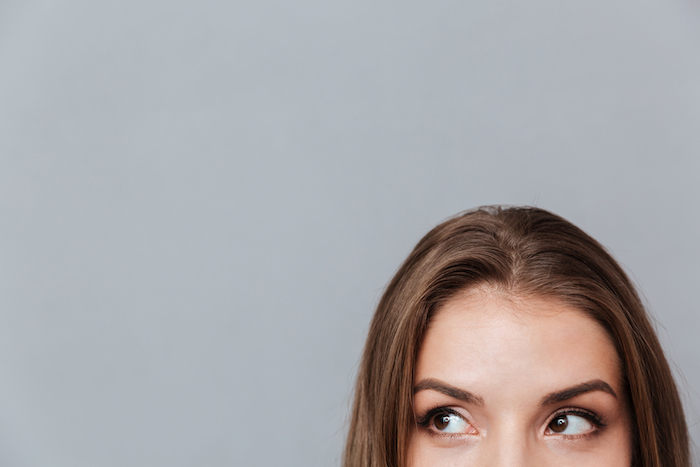 Cropped image of face of woman looking aside. Isolated gray background